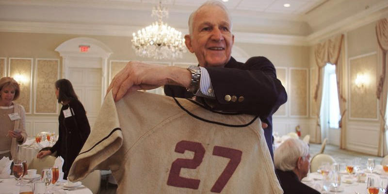 Boys' High alumnus Tommy Tillman holds up an old jersey from the high school. It closed in 1947.