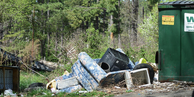 On the grounds of Brannon Hill Condominiums, piles of trash blanket the complex.