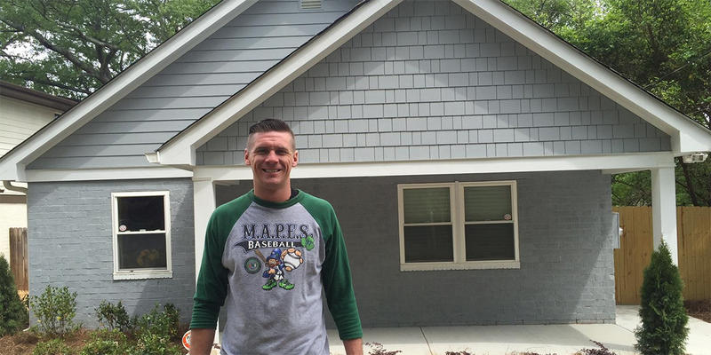 Atlanta police Officer Mike Costello stands in front of his new home in Atlanta's Edgewood neighborhood. Costello bought the house through a program to help police officers buy houses within the cities they serve.