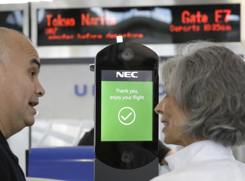 U.S. Customs and Border Protection officer Sanan Jackson, left, helps a passenger navigate one of the new facial recognition kiosks Wednesday at a United Airlines gate before boarding a flight to Tokyo at George Bush Intercontinental Airport in Houston.