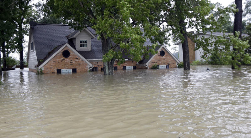 A home is surrounded by floodwaters from Tropical Storm Harvey on Monday, Aug. 28, 2017, in Spring, Texas.