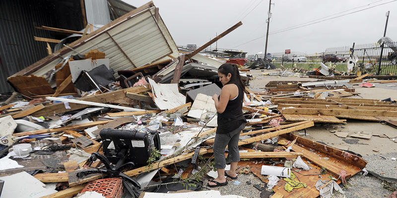 Jennifer Bryant looks over the debris from her family business destroyed by Hurricane Harvey. Atlanta medical professionals and businesses are on their way to Texas to aid in the rescue and repair efforts.