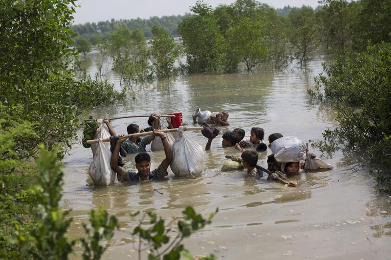 A Rohingya family reaches the Bangladesh border after crossing a creek of the Naf river on the border with Myanmmar, in Cox's Bazar's Teknaf area on Tuesday, Sept. 5.
