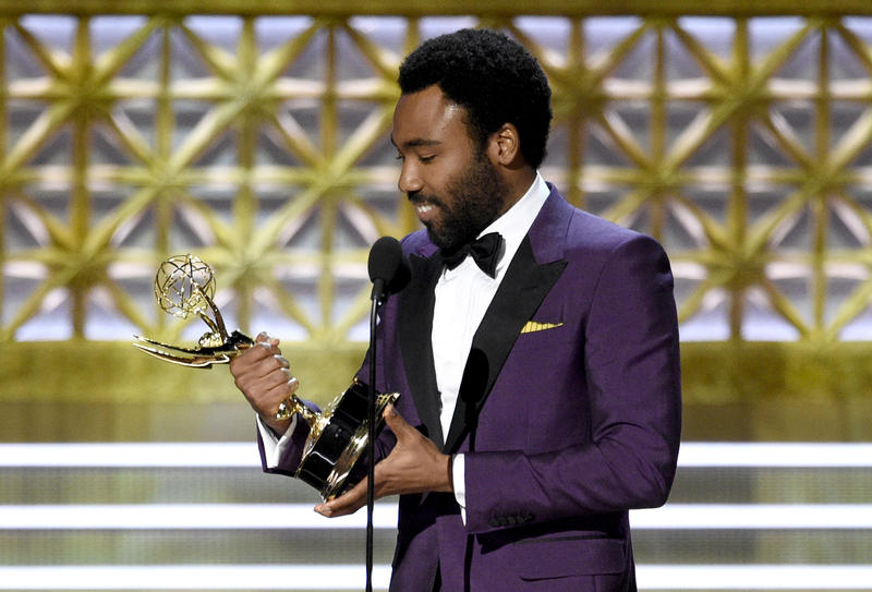 """Donald Glover accepts the award for outstanding directing for a comedy series for the """"Atlanta"""" episode """"B.A.N."""" at the 69th Primetime Emmy Awards on Sunday, Sept. 17, 2017, at the Microsoft Theater in Los Angeles."""