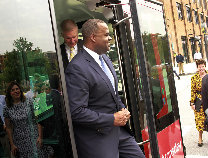 Atlanta Mayor Kasim Reed hops off the self-driving shuttle at Ponce City Market.