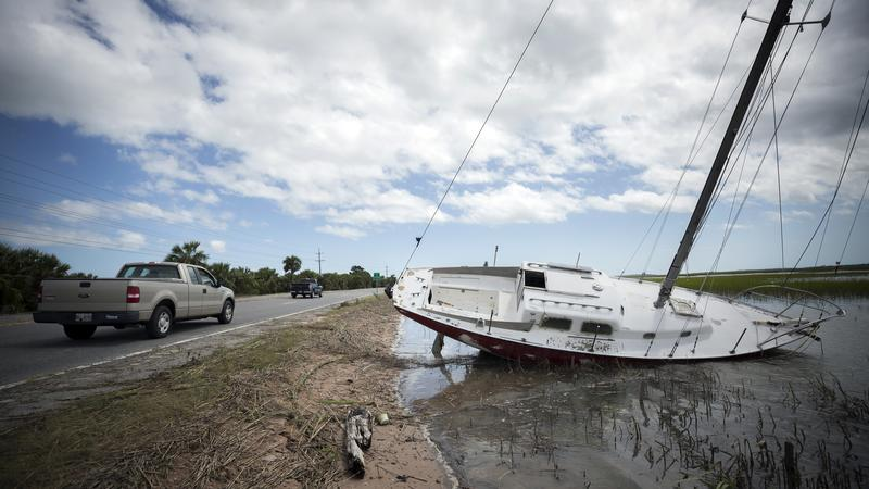 Residents drive past a sailboat washed onto the road to Tybee Island, Ga., Tuesday, Sept., 12, 2017, after the state opened Highway 80 after Tropical Storm Irma flooded island yesterday.