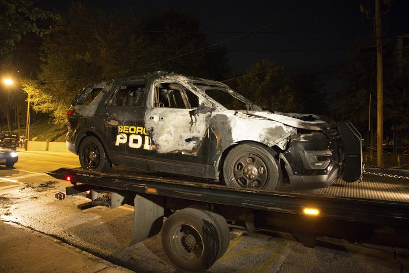A truck carries a burned Georgia Tech police vehicle Monday in front of the police station on campus in Atlanta. The car was allegedly set ablaze by protesters demonstrating against a shooting that resulted in the death of student Scout Schultz.