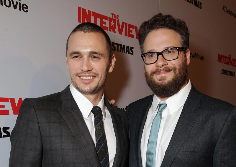 'The Interview's' stars James Franco and Seth Rogen pose for pictures at the movie's premiere.