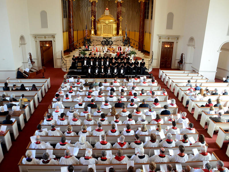 At the renewal of vows for the clergy of the Episcopal Church, the clergy is dressed in white robes in the center section of the sanctuary at The Temple in Atlanta.