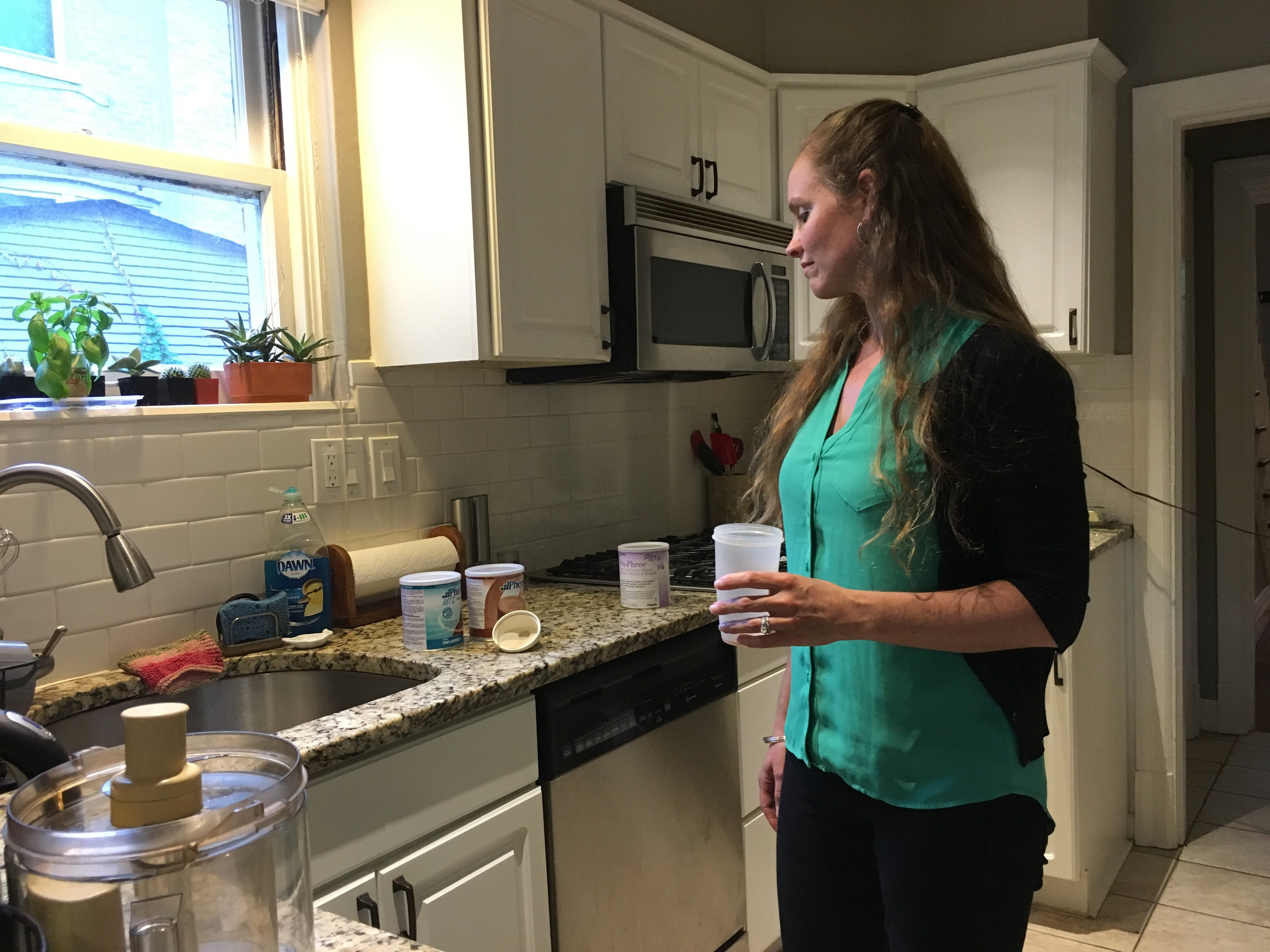 Amanda Moller prepares her formula in her home in University City, Missouri. The formula is vital to treat a rare condition, but her insurer doesn't cover it.