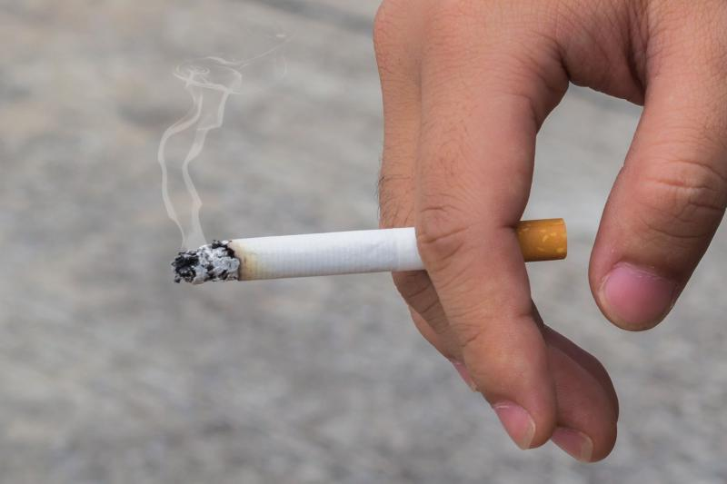 photo of burning cigarette in hand