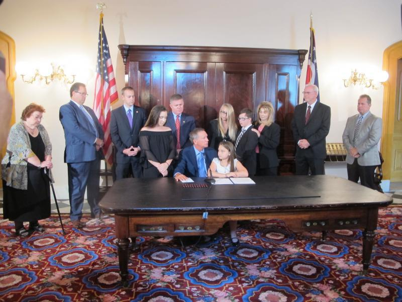 Photo of Gov. Kasich preparing to sign Judy's Law