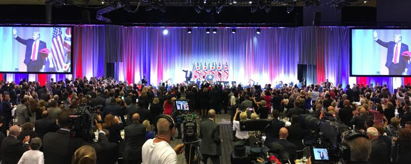 President Donald Trump leaves the stage as the crowd applauds.