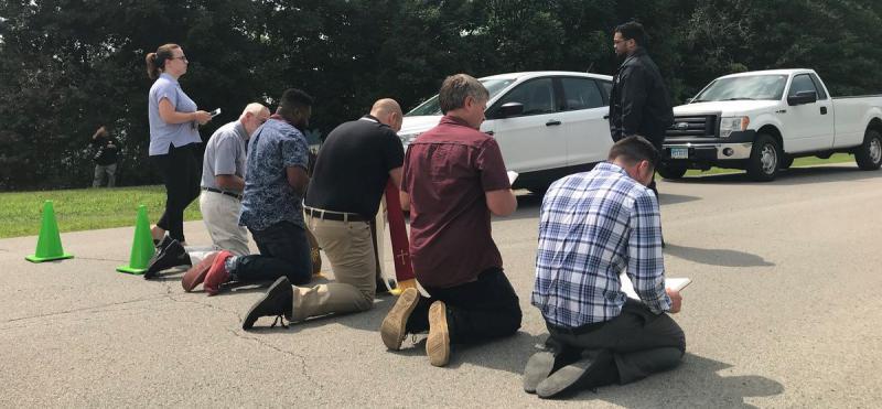 photo of protestors kneel in the prison driveway