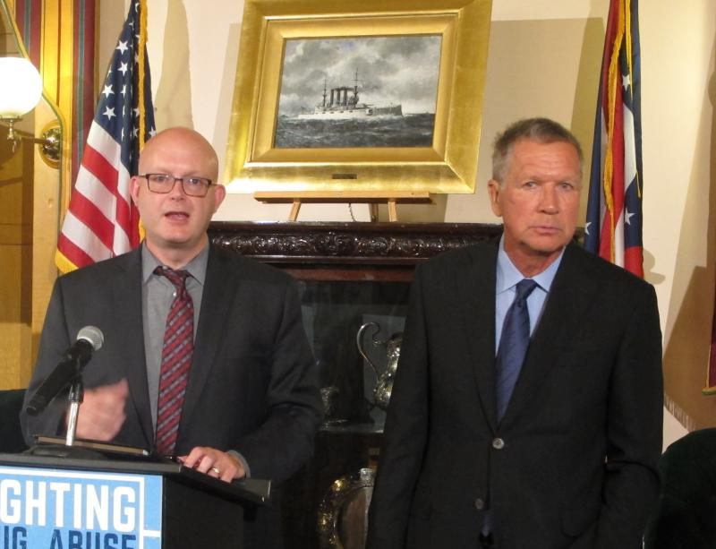A photo of Jim Tassie, assistant director of Ohio Medicaid, and Gov. John Kasich talking about the change in the rule requiring background checks on Medicaid providers.