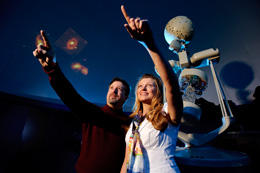 Astronomy Professor Mike Brotherton and recent graduate student Sabrina Cales enjoy images at the UW planetarium.