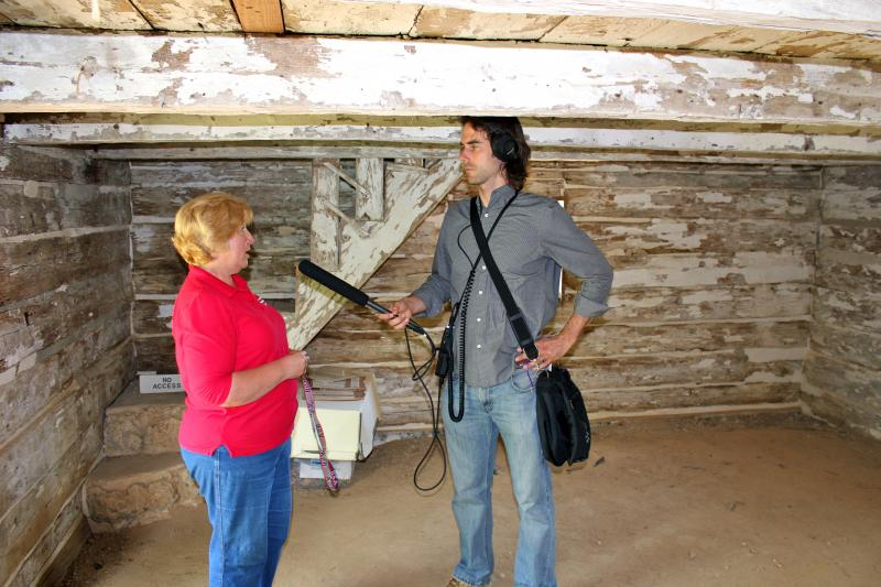 Sotterley Education Director Jeanne Pirtle (l) and WYPR's Bret Jaspers inside the cabin.